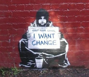 "Photo of a young man seated on street holding a sign that says, ""Keep your coins, I want change."""